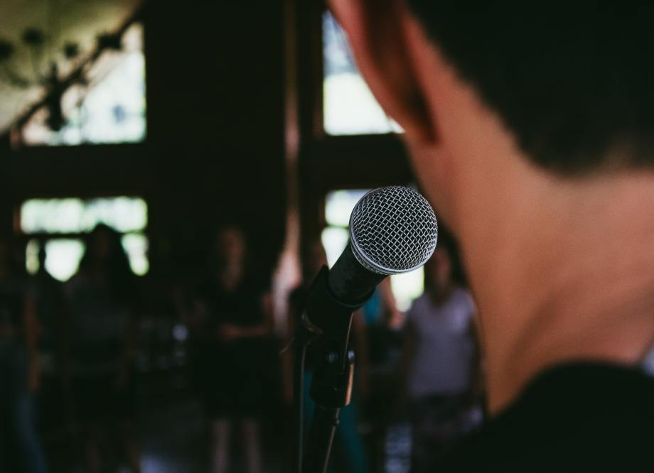 Man stands in front of a microphone looking out on an audience.