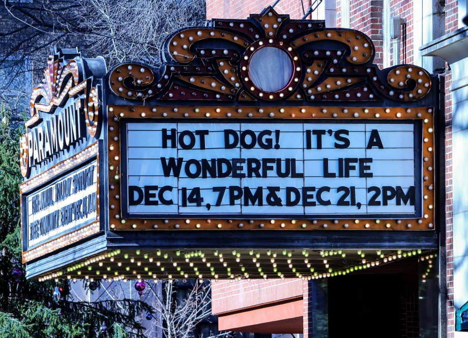 """a theater marquee bears the words """"Hot dog! It's a wonderful life!"""" and times for showings of the movie."""