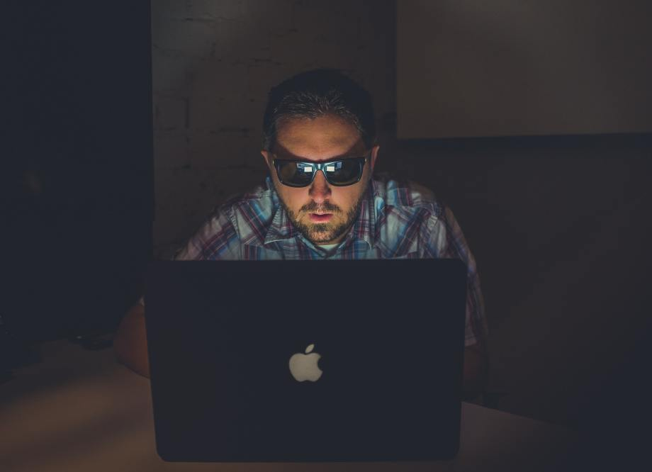 man viewing a laptop computer screen in a dark room. he is wearing sunglasses.
