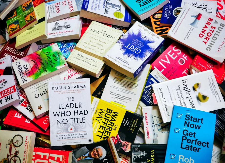 a variety of self-help books in a large, sprawling pile
